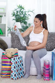 Pregnancy at home with shopping bags — Stock Photo