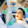 Stock Photo: Dentist with nurse doing procedure on patient
