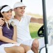 Smiling couple in golf cart — Stock Photo #14555297