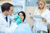 Dentist and a nurse with patient in office — Stock Photo