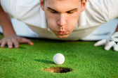 Golfer blowing in the ball — Stockfoto