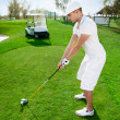 Golfer is preparing to hit golf ball - Stock Photo