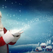 Santa Claus blowing snow to little town — Stock Photo #16942949