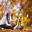 Beautiful girl with book in the autumn park — Stok fotoğraf