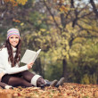 Woman with book in autumn park — Stock Photo #16943699