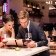 Smiling couple decide what to order — Stockfoto