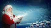 Santa Claus blowing snow to little town — Stock Photo