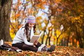 Belle fille avec livre dans le parc en automne — Photo