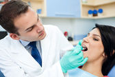 Dentist is treating teeth of the patient — Stock Photo