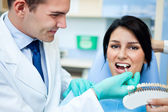 Dentist examining a whiteness of teeth of a patient — Foto Stock