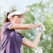 Woman playing golf - Stockfoto
