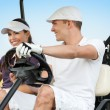 Happy young couple on golf course - Stock Photo