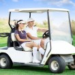 Couple in golf car - Stock Photo