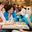 Four college chatting in a coffee shop — Stock Photo