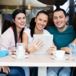 Stock Photo: Smiling group of teenagers at cafe