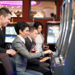 Постер, плакат: Young gambling in the casino on slot machines