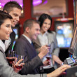 Young enjoying to play slot machines — 图库照片