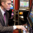 Men gambling in the casino on slot machines — Stock Photo #20181923