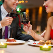 Attractive young couple drinking red wine in restaurant  — Stok fotoğraf