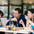 Foto Stock: Cheerful friends chatting while lunch