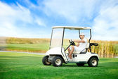 Young man driving golf buggy — Stock Photo