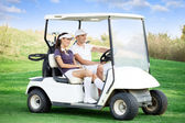 Couple in golf car — Stok fotoğraf