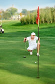 Golfer lining up a putt. — Stock Photo