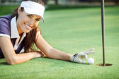 Happy woman golf pushing golf ball into the hole — Stock Photo