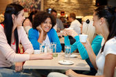 Fyra college chattar i ett kafé — Stockfoto