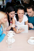 Group of teenagers using tablet touch — Stock Photo