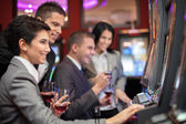 Young enjoying to play slot machines — Stok fotoğraf