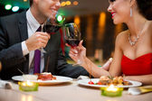 Attractive young couple drinking red wine in restaurant — Stock Photo