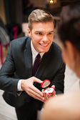 Young man proposing to his pretty girlfriend — Stok fotoğraf