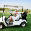 Couple in buggy in golf course — Stock Photo