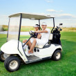 Happy couple driving a golf-cart - Stock Photo