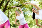 Young women stretching in park — Stock Photo