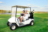Happy couple driving a golf-cart — 图库照片
