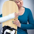 Woman with broken arm hugging her snowboard — Stock Photo