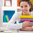 Cheerful girl hugging books — Stockfoto