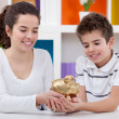 Two children holding piggybank — Stock Photo