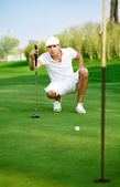 Young golfer lining up a putt — Foto de Stock