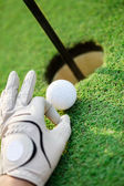 Golf ball on green grass next hole — Stock Photo