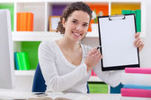 Girl sitting on her desk showing blank paper — Stock Photo