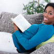 African woman relaxing with a book — Stock Photo