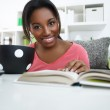 Smiling African student learning at home — Stock Photo #24891121