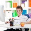 Smiling boy using a computer — Stockfoto