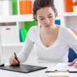 Stock Photo: Woman using a graphic tablet and pen