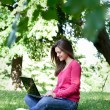 Pretty girl using laptop in park — Stock Photo