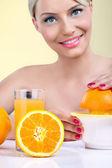 Beautiful woman making orange juice — Stock Photo