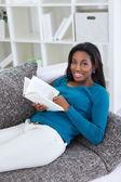 Smiling black woman reading book — Stock Photo